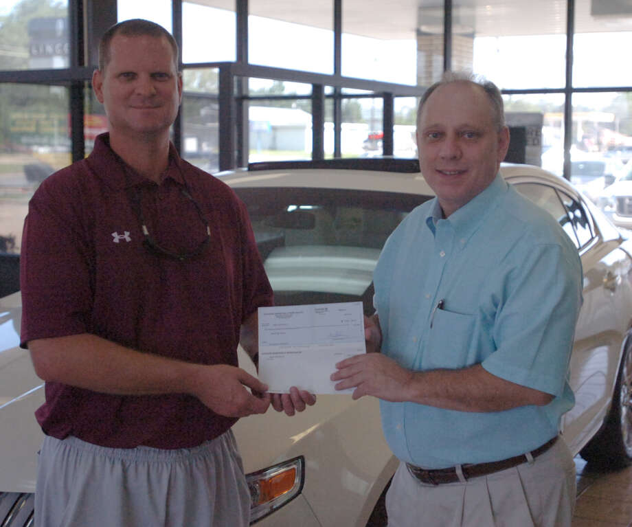 Jasper Athletic Director Darrell Barbay accepts a donation from Jasper Ford Lincoln Mercury General Manager Allan Chesnut for $1,760. The check will be posted to the Jasper High School girl athletics account. Photo: Jimmy Galvan