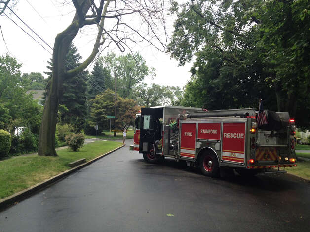 Stamford Fire & Rescue crews block off a portion of Downs Avenue in Shippan after a tree struck a house. Photo: John Nickerson