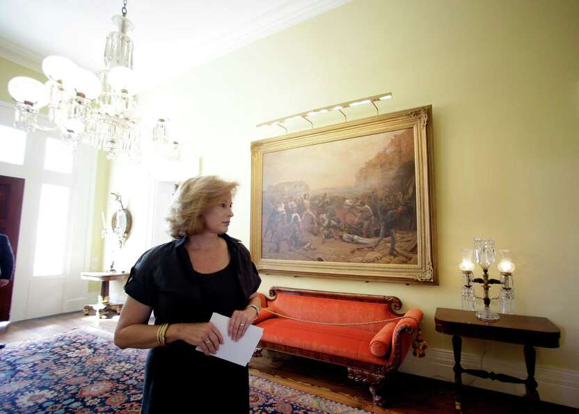 Texas first lady Anita Perry walks past a painting depicting the battle of the Alamo as she gives a