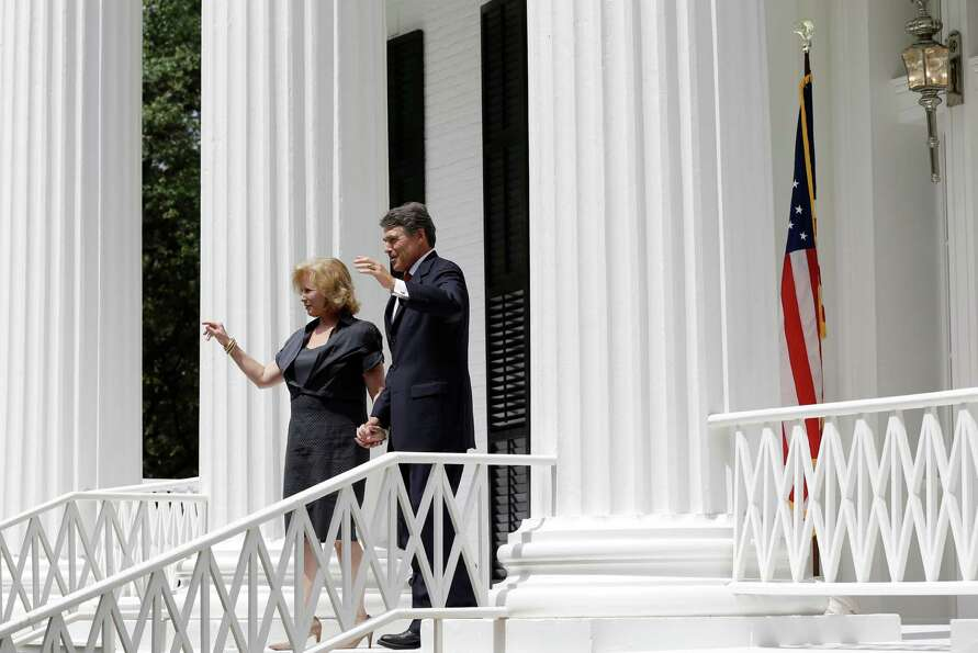 Texas Gov. Rick Perry, right, and his wife Anita Perry, left, walk out of the Texas Governor's Mansi