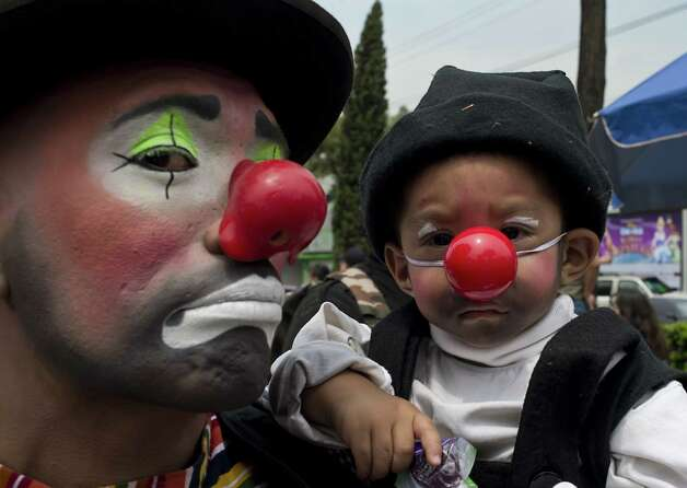 A clown and his son pose during a pilgrimage to the Virgin of Guadalupe's basilica, Mexico's patron saint, in Mexico City on July 18, 2012. Hundreds of clowns take part in the annual pilgrimage to the sanctuary of the Virgin. AFP PHOTO/Omar TorresOMAR TORRES/AFP/GettyImages Photo: OMAR TORRES, AFP/Getty Images / AFP