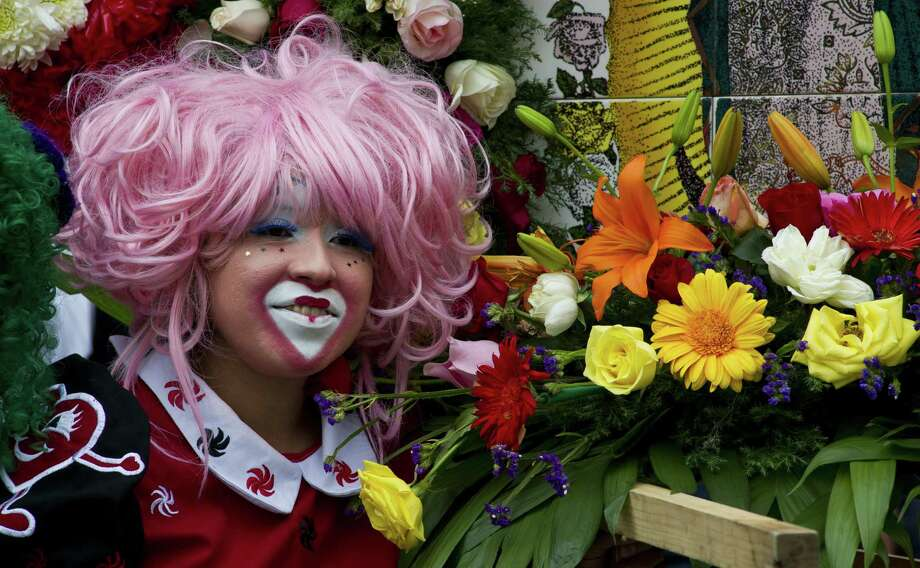 A clown smiles as she poses next to flowers during a pilgrimage to the Virgin of Guadalupe's basilica, Mexico's patron saint, in Mexico City on July 18, 2012. Hundreds of clowns take part in the annual pilgrimage to the sanctuary of the Virgin. AFP PHOTO/Omar TorresOMAR TORRES/AFP/GettyImages Photo: OMAR TORRES, AFP/Getty Images / AFP