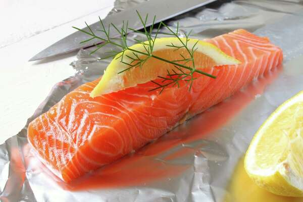 A raw fresh Salmon fillet, lemon slice and dill. (Fotolia.com)