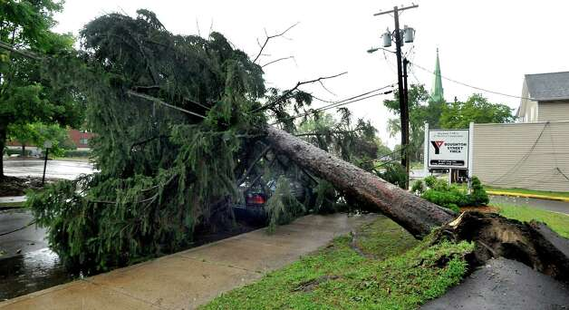 An uprooted tree lies across power lines and covers a parked car on Boughton Street in Danbury after a storm swept through the city on July 18, 2012. Photo: Michael Duffy