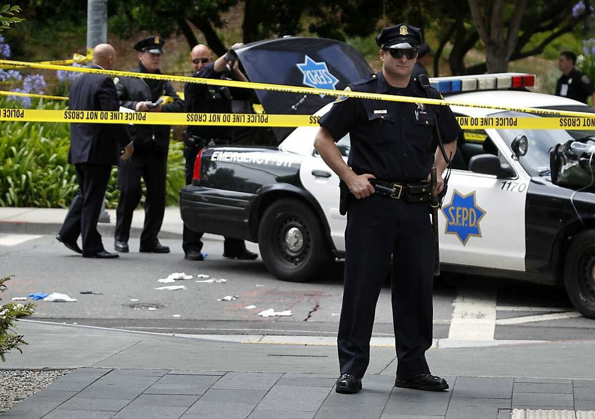 A police officer guards the scene of an officer involved shooting at Washington and Davis streets in San Francisco, Calif. on Wednesday, July 18, 2012. Officers shot and wounded a man who is suspected of stabbing a co-worker at the TCHO chocolate factory several blocks away.
