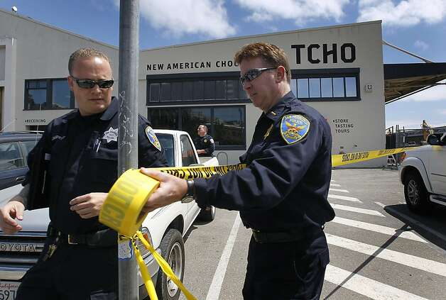 Police officers set up a perimeter around the TCHO chocolate factory on Pier 17 while they investigate a stabbing incident with one employee another with a box cutter in San Francisco, Calif. on Wednesday, July 18, 2012. The suspect was later shot and wounded by officers at Washington and Davis streets, several blocks away. Photo: Paul Chinn, The Chronicle