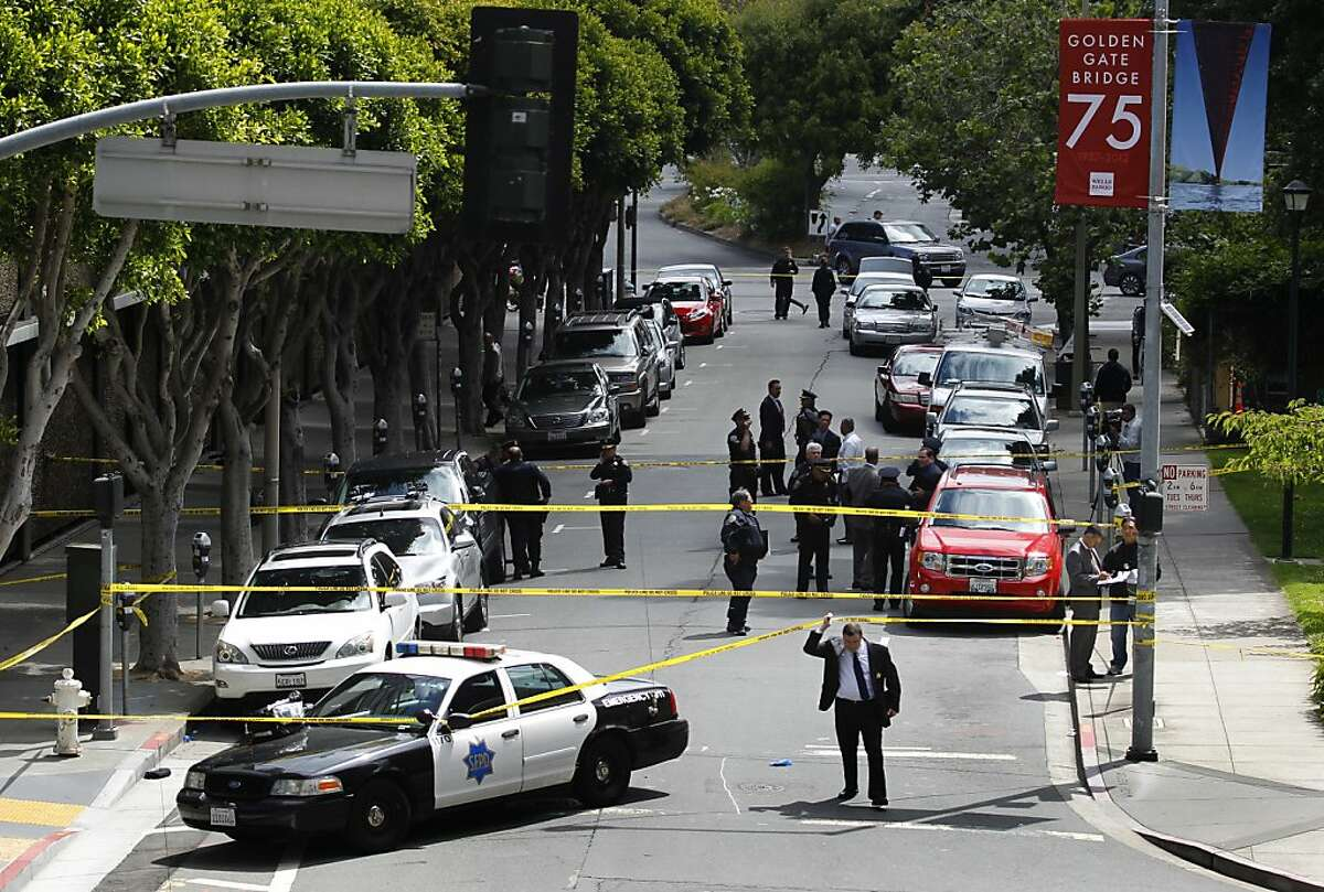 Police officers investigate an officer involved shooting at Washington and Davis streets in San Francisco, Calif. on Wednesday, July 18, 2012. Officers shot and wounded a man who is suspected of stabbing a co-worker at the TCHO chocolate factory several blocks away.