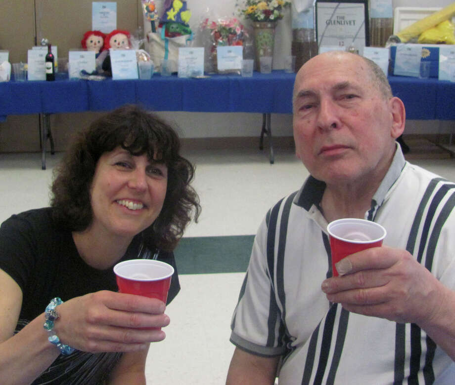 Denise Becker, the wife of Frank Becker Jr., and her father, Joel DiPaola, toast Mr. Becker during a fundraising event held recnelty at the United Methodist Church in New Milford  Courtesy of the Becker family Photo: Contributed Photo