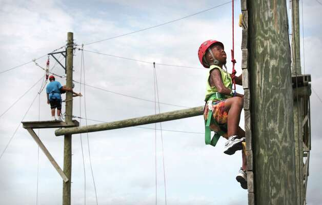 Sean Bigelow, 11, of Georgetown, TX, climbs a pole on a high ropes course, that ends on a zipline.  Campers from all over Texas take part in the Texas Burn Survivor Society's Pediatric Burn Camp, called Camp David, held at Texas Lion's Camp in Kerrville, TX.  Wednesday, July 18, 2012. Photo: Bob Owen, San Antonio Express-News / © 2012 San Antonio Express-News