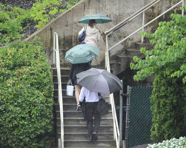 Commuters carry umbrellas as they climb the stairs to the central Greenwich train station during the afternoon rain storm, Wednesday afternoon, July 18, 2012. Photo: Bob Luckey / Greenwich Time