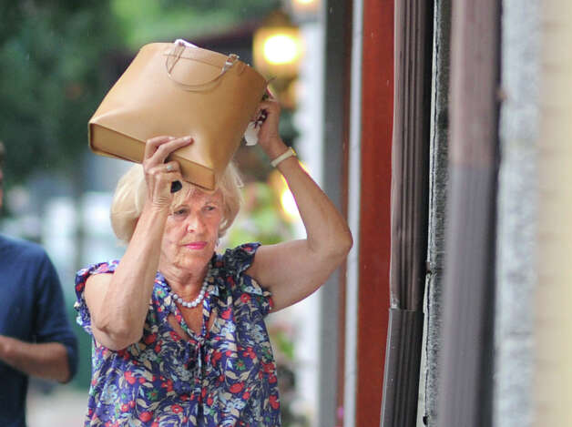 Irmgard Gwilliam of Westport uses her handbag to shield herself from the rain before ducking into a store on Greenwich Avenue during the afternoon storm, Wednesday, July 18, 2012. Photo: Bob Luckey / Greenwich Time