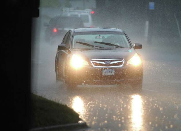 A car makes it way through a downpour on West Putnam Avenue during the afternoon rain storm in Greenwich, Wednesday afternoon, July 18, 2012. Photo: Bob Luckey / Greenwich Time
