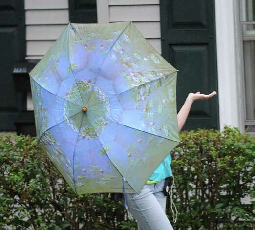 A woman walking on Byram Road sticks her hand out from under her umbrella to check for rain during one of the afternoon storms that hit the Greenwich area, Wednesday afternoon, July 18, 2012. Photo: Bob Luckey / Greenwich Time
