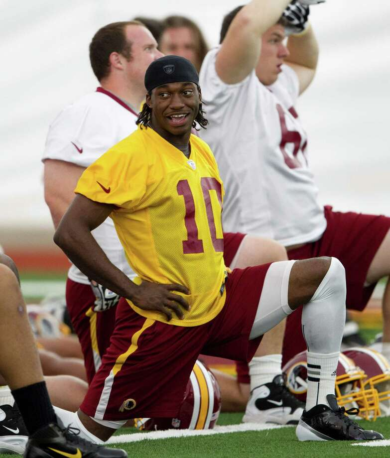 FILE - This May 21, 2012 file photo shows Washington Redskins rookie quarterback Robert Griffin III stretching during practice in Ashburn, Va. Griffin has agreed to terms on a contract with the Redskins. Griffin's agent, Ben Dogra, told The Associated Press that the Heisman Trophy-winning quarterback agreed to terms and will be in Redskins rookie camp on Wednesday, July 18, 2012. Photo: AP
