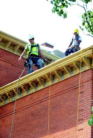 Workers repair the roof of the Alternative Center for Excellance in Danbury Wednesday, July 18, 2012. The heat has caused some roofers to shorted their work days this summer. Photo: Michael Duffy