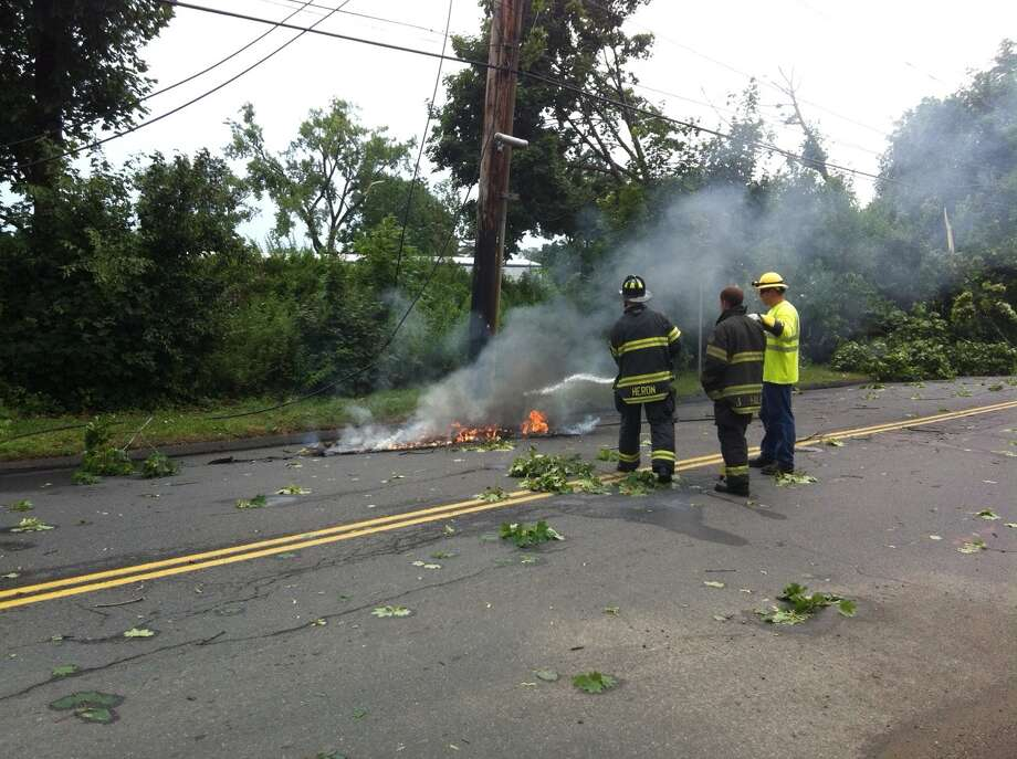 Crews try to put out wires on triangle that caught the asphalt on fire. Photo: Dirk Perrefort, News Times / News Times