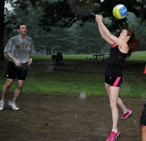Kate James, right, plays volleyball at Scalzi Park through thunderstorms which rolled through Stamford on Wednesday, July 18, 2012. Photo: Lindsay Niegelberg / Stamford Advocate