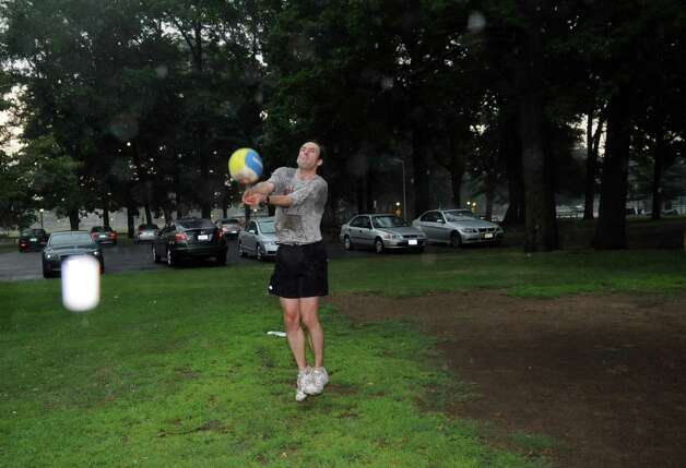 Tim Vanhooser plays volleyball at Scalzi Park through thunderstorms which rolled through Stamford on Wednesday, July 18, 2012. Photo: Lindsay Niegelberg / Stamford Advocate