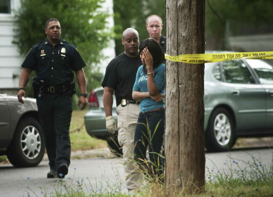 MICHIGAN: An emotional woman who police say crossed the tape at a crime scene turns away as officers prepare to handcuff her in Flint. A suspect has been arrested after two men and a woman were fatally shot and a second woman, who was wounded in the shooting, managed to flee the house and alert authorities, police said. Photo: AP