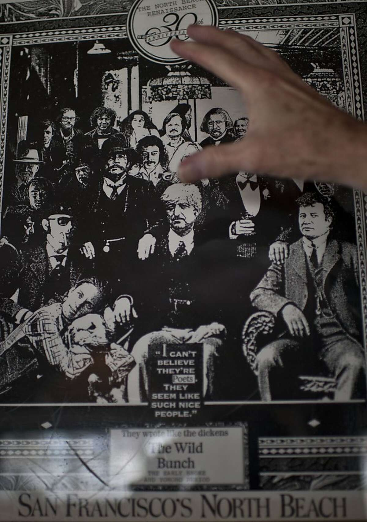 AD Winans shows himself in a smaller version of a 1970's poster of poets gathered at Vesuvio bar, in the North Beach neighborhood of San Francisco, Calif on Friday, July 13, 2012.