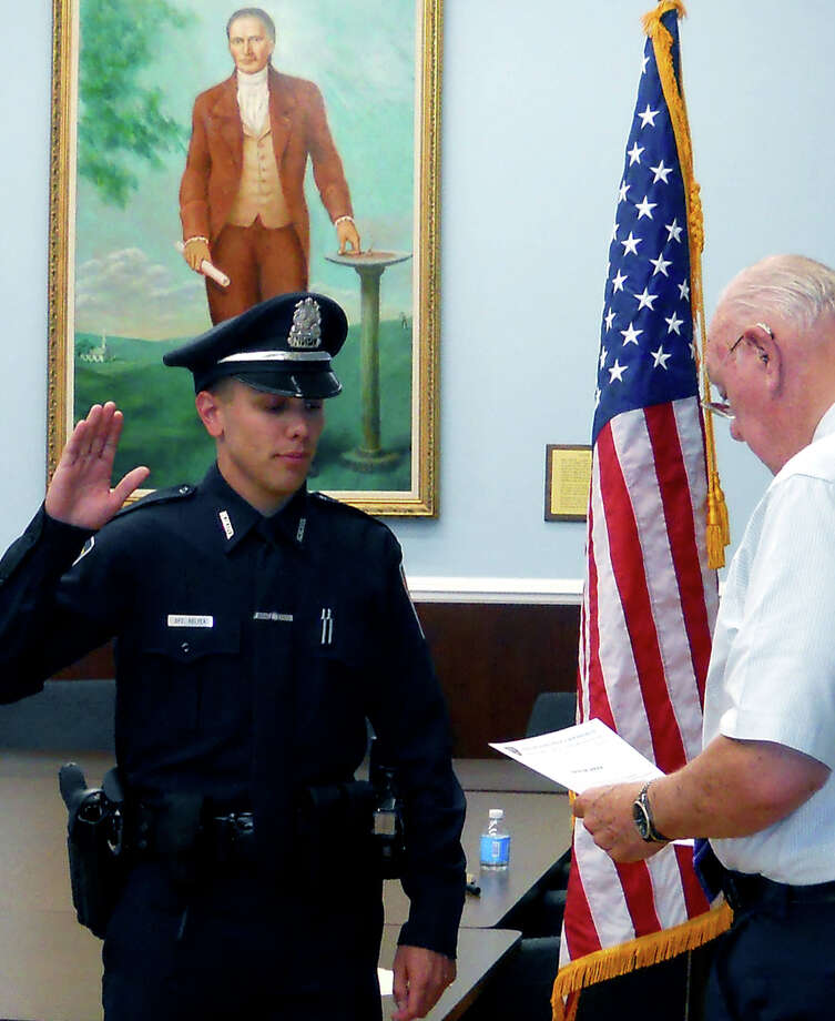 Officer Alex Relyea is sworn in to serve in the New Milford Police Department by Town Clerk George Buckbee during a July 11, 2012 ceremony in the E. Paul Martin Meeting Room at New Milford Town Hall.  Courtesy of the New Milford Police Department Photo: Contributed Photo