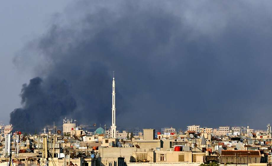 In this citizen journalist image, smoke billows over Damascus, Syria, Wednesday, July 18, 2012. A bomb ripped through a high-level security meeting Wednesday in Damascus, killing three top regime officials — including President Bashar Assad's brother-in-law — in the harshest blow to Syria's ruling family dynasty and the rebels' boldest attack in the country's civil war. Syrian state-run TV said the blast came during a meeting of Cabinet ministers and senior security officials in Damascus, which has seen four straight days of clashes between rebels and government troops. (AP Photo) Photo: Associated Press