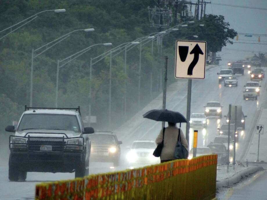 A woman crosses Northwest Military Highway near Wurzbach Parkway as traffic approaches during a steady rainfall on Wednesday afternoon, July 18, 2012. Photo: Billy Calzada, San Antonio Express-News / San Antonio Express-News