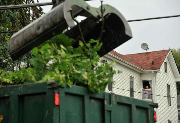 Angelica Vega looks out her window to watch City crews remove a tree that was blocking Coal Pit Hill Road in Danbury after a strong thunderstorm went through the city on Wednesday, July 18, 2012. Photo: Jason Rearick / The News-Times