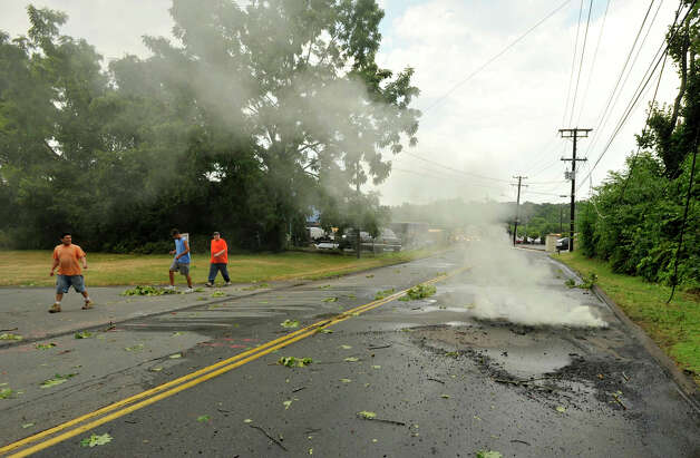 A live electrical wire fell in the eastbound lane of Triangle Street in Danbury melting the road after a strong thunderstorm went through the city on Wednesday, July 18, 2012. People are seen here observing the smoldering asphalt after the electricty was disconnected. Photo: Jason Rearick / The News-Times