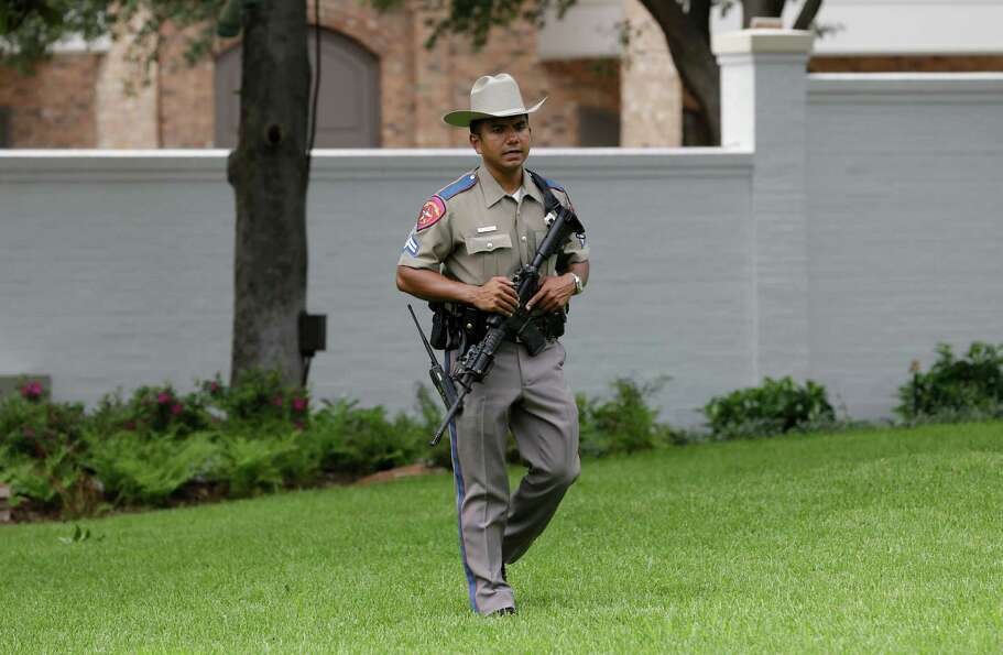 A state trooper stands guard over the restored Texas Governor's Mansion Wednesday, July 18, 2012, in