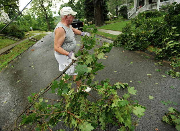 Skip Clapp removes a large branch that fell in front of his house on High Street in Bethel after a strong thunderstorm went through the town on Wednesday, July 18, 2012. Photo: Jason Rearick / The News-Times