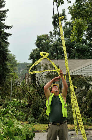 Danbury Forestry worker Mark Miller attaches caution tape onto wires that hang over Coal Pit Hill Road in Danbury after a strong thunderstorm went through the city on Wednesday, July 18, 2012. Photo: Jason Rearick / The News-Times