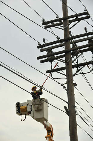A worker with CL&P does line work along Triangle Street in Danbury after a strong thunderstorm went through the city on Wednesday, July 18, 2012. Photo: Jason Rearick / The News-Times