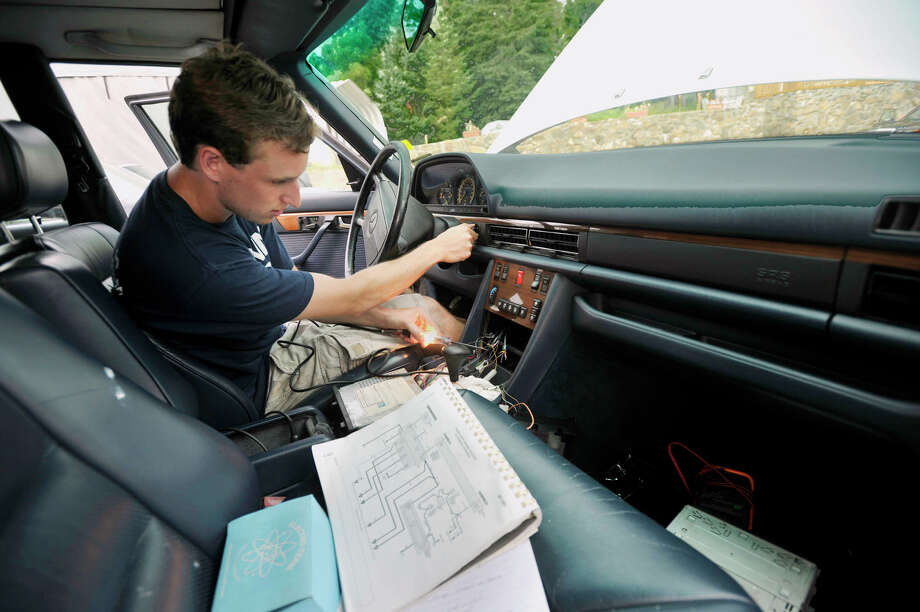Dayton Horvath, a 2012 UConn graduate and a 2008 Newtown High School graduate, replaces the radio in his newly purchased 1989 Mercedes 420 SEL outside his family's home in Newtown on Wednesday, July 18, 2012. Horvath will be traveling cross-country to the University of California at Santa Barbara, where he will work toward his Ph.D. in chemistry. Photo: Jason Rearick