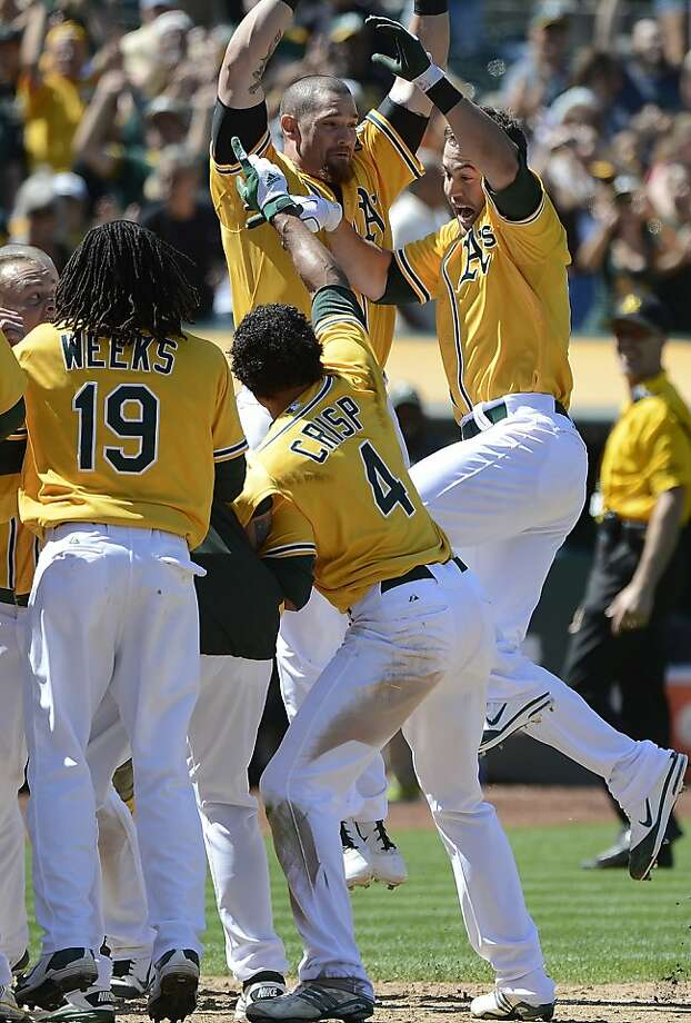 OAKLAND, CA - JULY 18:  Brandon Hicks #18 (R) of the Oakland Athletics celebrates with Jonny Gomes #31, Jemile Weeks #19 and Coco Crisp #4 after Hicks hit a walk-off solo home run in the bottom of the ninth inning to defeat the Texas Rangers 4 to 3 at O.co Coliseum on July 18, 2012 in Oakland, California.  (Photo by Thearon W. Henderson/Getty Images) Photo: Thearon W. Henderson, Getty Images