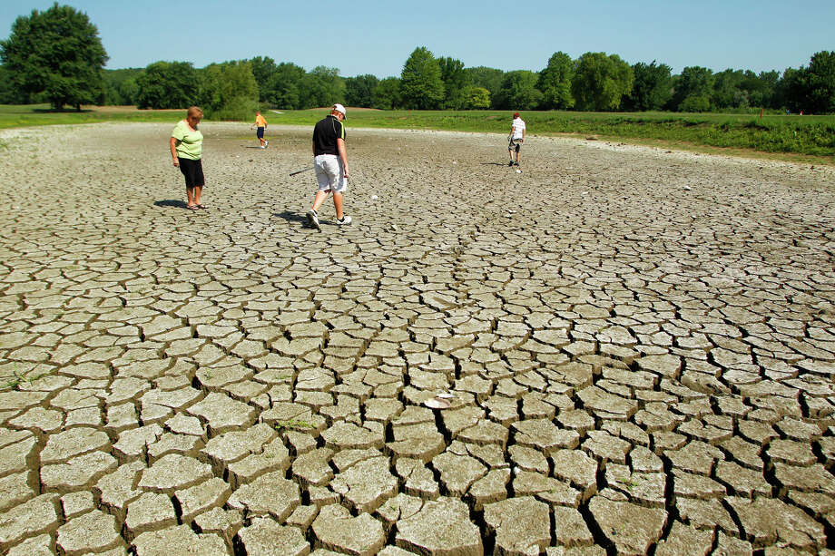 Golfers look for a ball in a dry pond at Lafayette Golf Course in Indiana.  Three-fifths of the U.S. land mass has been hard hit by lack of rain. Photo: John Terhune / Journal & Courier