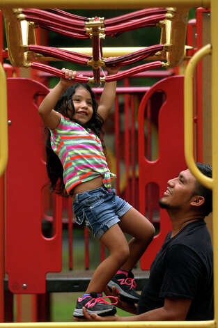 Abdias Martinez, of Bridgeport, gives his daughter Shirley, 5, a helping hand to get across the monkeybars as they enjoy time at a playground at Beardsley Park in Bridgeport, Conn. on Wednesday July 18, 2012. Photo: Christian Abraham / Connecticut Post