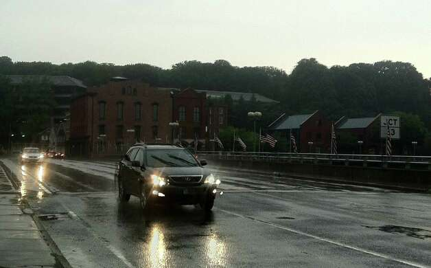 Cars navigate the Route 1 bridge over the Saugatuck River in downtown Westport under threatening skies as rain started falling Wednesday evening. Photo: Paul Schott / Westport News