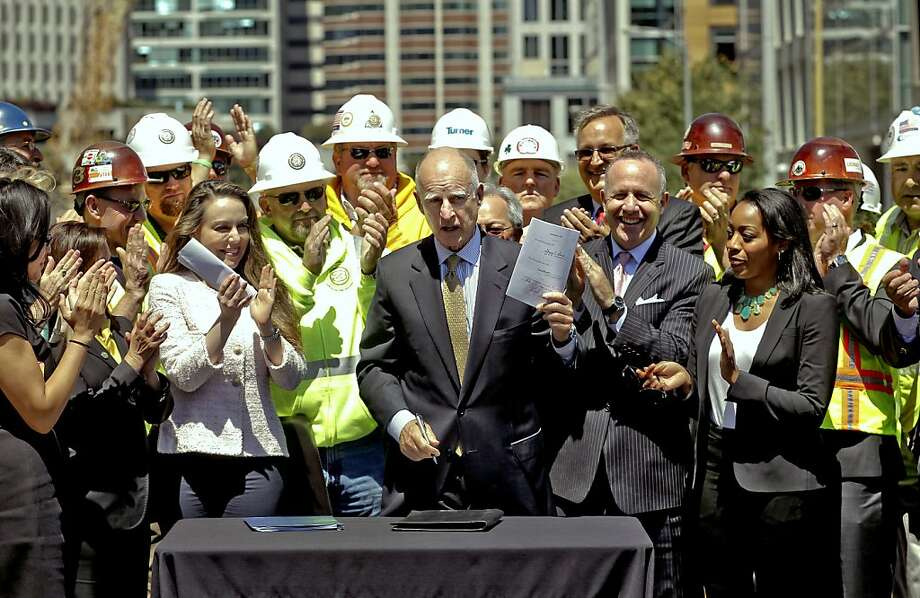 Gov. Jerry Brown stands with workers at the Transbay Transit Center construction site in San Francisco in July 2012 as he shows off legislation that backed high-speed rail. Photo: Michael Macor, The Chronicle