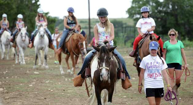 Campers at Camp David ride horses, with counselors by their side, as one of the many activities offered.  Campers from all over Texas take part in the Texas Burn Survivor Society's Pediatric Burn Camp, called Camp David, held at Texas Lion's Camp in Kerrville, TX.  Wednesday, July 18, 2012. Photo: Bob Owen, San Antonio Express-News / © 2012 San Antonio Express-News