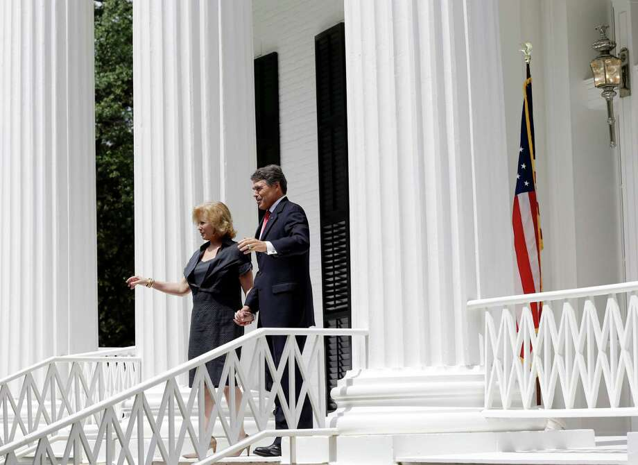 Texas Gov. Rick Perry, right, and his wife Anita Perry, left, walk out of the Texas Governor's Mansion for a news conference, Wednesday, July 18, 2012, in Austin, Texas. After four years and a $25 million restoration project, the historic Texas Governor's Mansion that was nearly destroyed by fire is complete. (AP Photo/Eric Gay) Photo: Eric Gay, Associated Press / AP