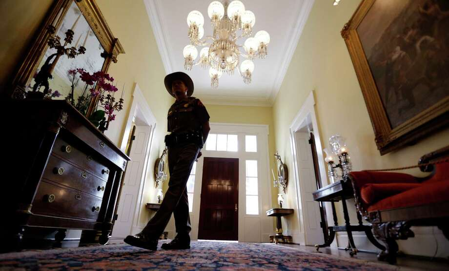 A Texas state trooper patrols the Texas Governor's Mansion Wednesday, July 18, 2012, in Austin, Texas. After four years and a $25 million restoration project, the historic Texas Governor's Mansion that was nearly destroyed by fire is complete. Photo: Eric Gay, Associated Press / AP