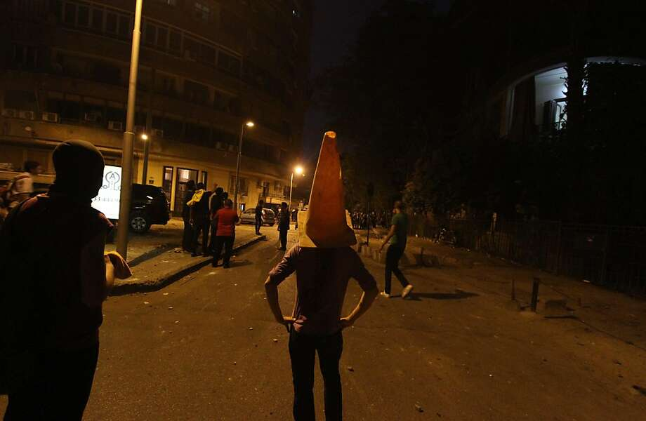 A man protects his head with a plastic traffic cone during clashes with Egyptian police as protesters gather close to the Syrian embassy in Cairo on July 18, 2012, hours after a bomb struck at the heart of Syria's senior command, killing at least three of President Bashar al-Assad's top brass in an attack claimed by rebels who warned of more carnage to come. AFP PHOTO/AHMED MAHMUDAHMED MAHMUD/AFP/GettyImages Photo: Ahmed Mahmud, AFP/Getty Images