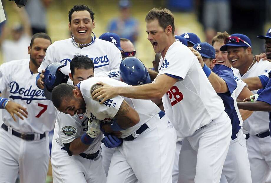 Los Angeles Dodgers' Matt Kemp, center, is swarmed by teammates, including Jamey Wright (28), after hitting a walkoff home run to give the Dodgers a 5-3 win over the Philadelphia Phillies in the 12th inning of a baseball game in Los Angeles, Wednesday, July 18, 2012. (AP Photo/Reed Saxon) Photo: Reed Saxon, Associated Press