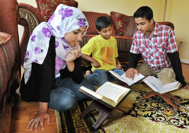 Haq family siblings, Iman Ahmed, 12, left, Fattah Ahmed, 9, and Taha Ahmed, 13, at right, memorizing and reciting the Koran at their Glenville home Wednesday July 18, 2012.   (John Carl D'Annibale / Times Union) Photo: John Carl D'Annibale / 00018493A