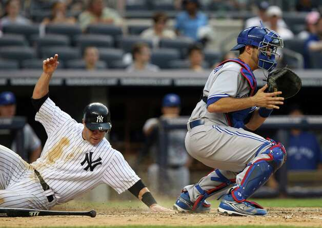 New York Yankees' Jayson Nix, left, slides safely home as Toronto Blue Jays catcher J.P. Arencibia waits for the throw during the sixth inning of a baseball game, Wednesday, July 18, 2012, at Yankee Stadium in New York. (AP Photo/Seth Wenig) Photo: Seth Wenig
