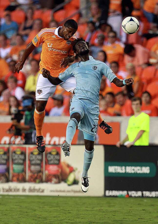Houston Dynamo defender Jermaine Taylor and Sporting KC forward Kei Kamara battle for the ball in the first half. Photo: Johnny Hanson, Houston Chronicle / © 2012  Houston Chronicle