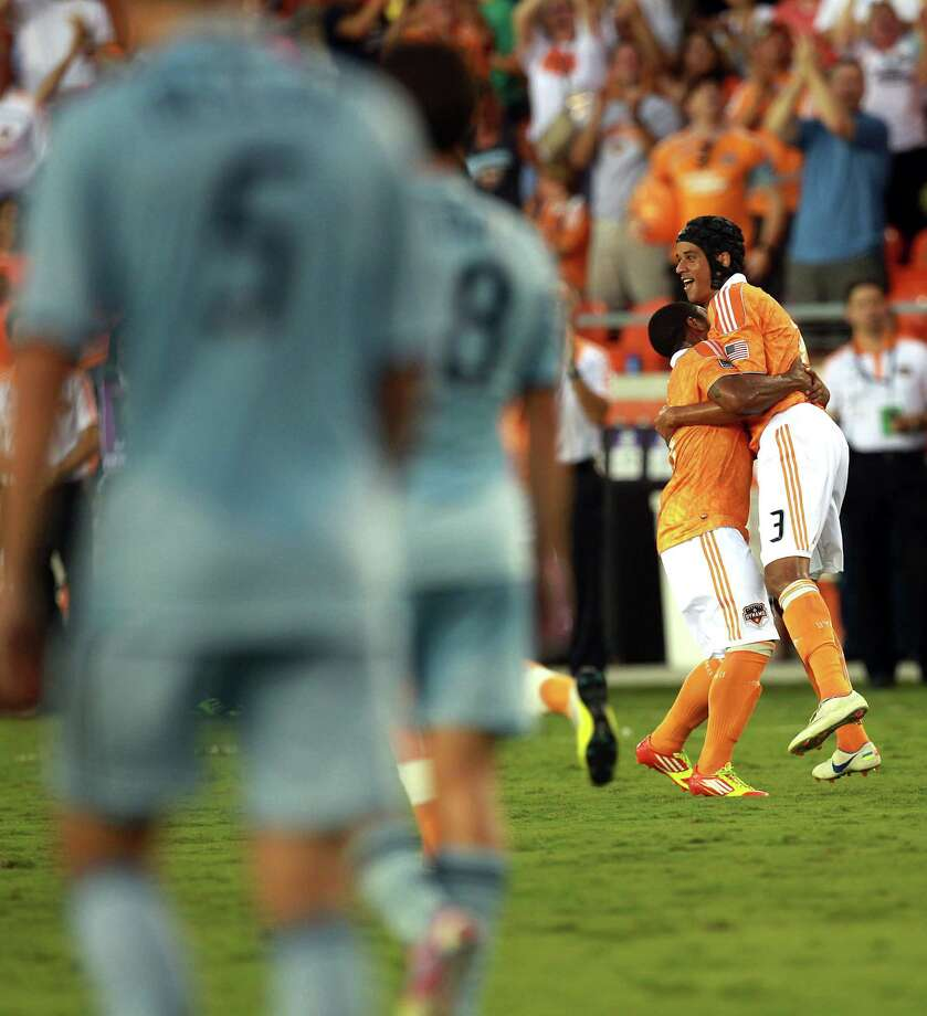Houston Dynamo forward Calen Carr (3), right, is hugged by  Houston Dynamo midfielder Corey Ashe (26) after Carr scored the first goal in the first half as the Houston Dynamo played Sporting Kansas City at BBVA Compass Stadium in a MLS soccer match Wednesday, July 18, 2012, in Houston. Photo: Johnny Hanson, Houston Chronicle / © 2012  Houston Chronicle