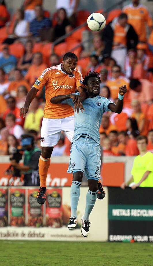 Houston Dynamo defender Jermaine Taylor (4) and Sporting KC forward Kei Kamara (23) battle for the ball in the first half as the Houston Dynamo played Sporting Kansas City at BBVA Compass Stadium in a MLS soccer match Wednesday, July 18, 2012, in Houston. Photo: Johnny Hanson, Houston Chronicle / © 2012  Houston Chronicle