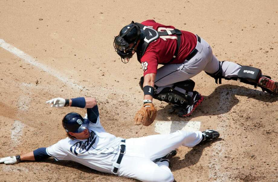 Chris Denorfia, left, provides the icing on the cake for the Padres, sliding safely past catcher Chris Snyder in the seventh inning for San Diego's eighth and final run Wednesday. Photo: Kent Horner / 2012 Getty Images